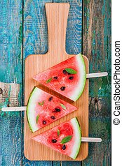 Slices of fresh juicy watermelon on a cutting board with mint