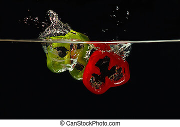 Slices of fresh red and green peppers falling into the water with a splash on black background