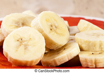 Slices of fruit of banana on red plate , close up
