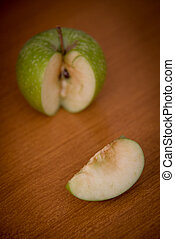 Slices of green healthy and antitoxin apple fruits on a brown table