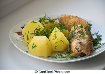 Slices of grilled sea bass with boiled potatoes on the plate.