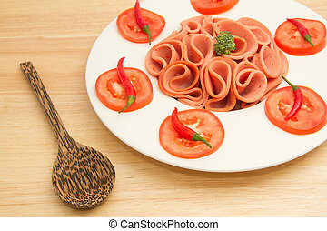 Slices of ham on white plate with tomato and chili