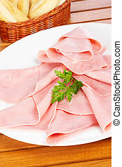 Slices of ham - Slices of tasty ham on white dish. Shallow ...