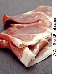 slices of Iberian ham, on stone base