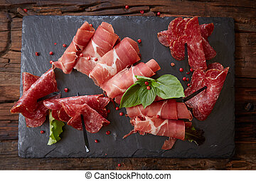 Slices of Italian prosciutto crudo or jamon with fresh basil leaves on a black background.