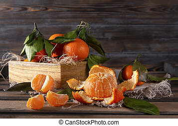 slices of juicy ripe tangerine on a wooden , whole tangerines in a box