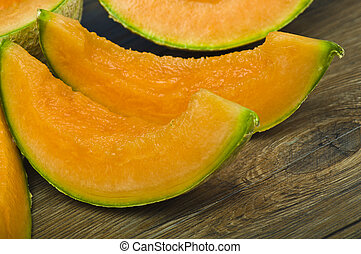 Slices of melon close up on wood table