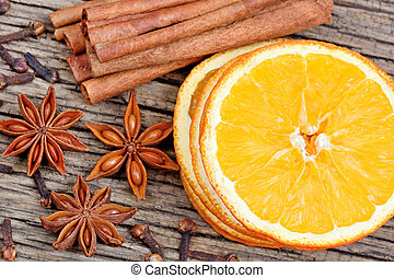 Slices of orange, cinnamon sticks, anise and cloves close-up