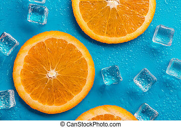 slices of orange  on a blue background, with ice around it and drops of water