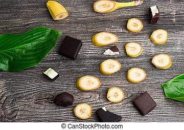 Slices of organic yellow bananas, chocolate candies and green leaves on wooden background