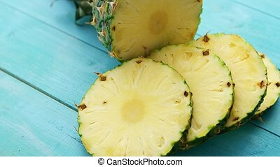Slices of pineapple on blue wood - From above shot of cut...