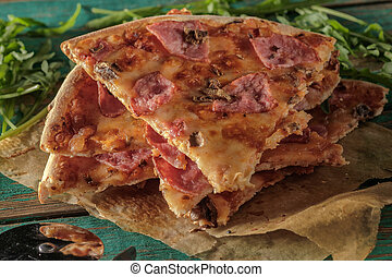 Slices of pizza on wooden table.