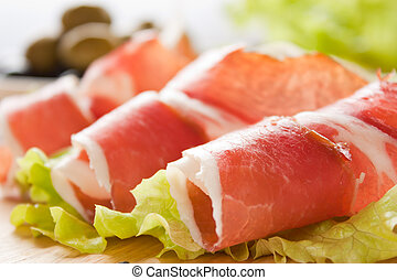 Slices of prosciutto rolled up and arranged on a lettuce...