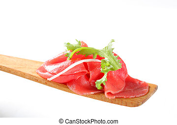 Slices of raw beef on spatula