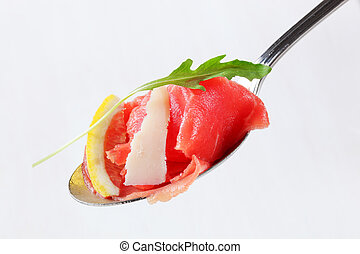 Slices of raw beef on spoon