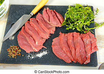 slices of raw beef with salad