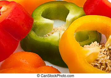 slices of red, green, yellow and orange pepper isolated on white background