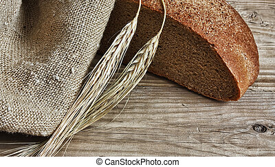 slices of rye bread and ears of corn on a wooden table