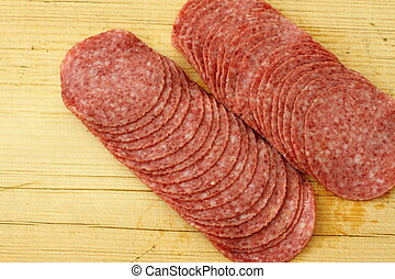 Slices of salami on cutting board