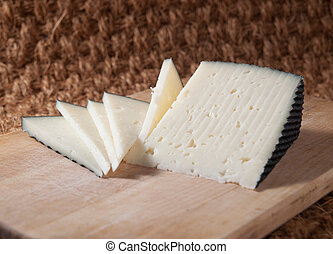 Slices of spanish cheese on a wooden board