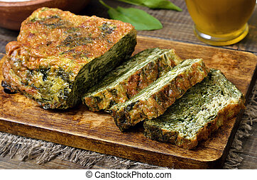 Slices of spinach bread on wooden cutting board