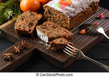 Slices of traditional English fruit cake with candied fruits served with clementines and star anise on oak board