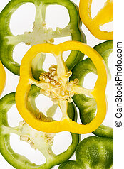 Slices of yellow and green pepper vegetables on white background.