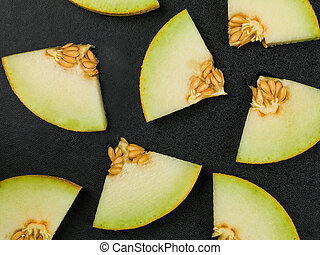 Slices or Chunks of Honeydew Melon on a Black Background