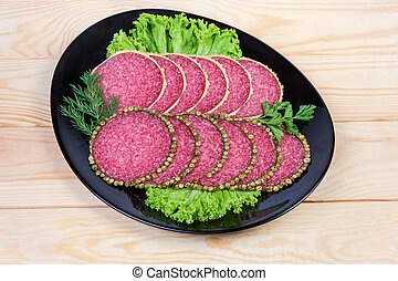 Slices salami with peppercorns and parmesan crust on black dish