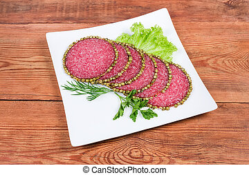 Slices salami with peppercorns crust with greens on square dish