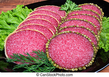 Slices salami with two various crust on black dish closeup