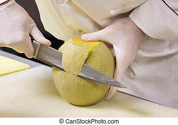 A prep cook slicing a cantaloupe.