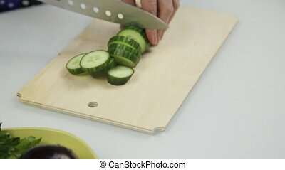 Slicing cucumber for lettuce. Cutting vegetables on wooden kitchen board.