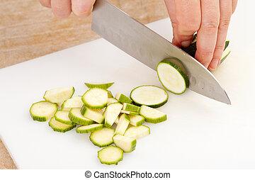 slicing cucumber on a white cutting board closeup