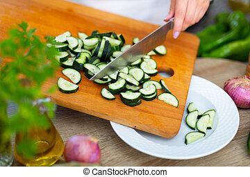 Slicing fresh cucumber on cutting board