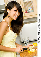 A beautiful young Asian woman slicing lemons in the kitchen