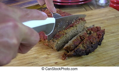 Slicing meatloaf topped with tomato paste
