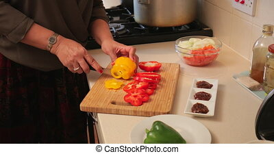 Slicing Peppers at Home - Close up shot of a woman slicing...
