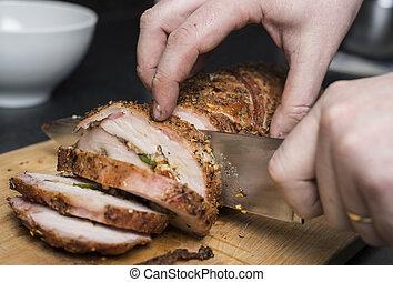 Slicing filled pork fillet on wooden board