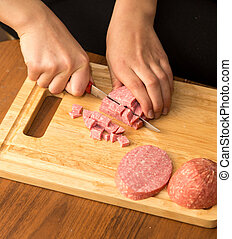 Slicing sausage with a knife on the board