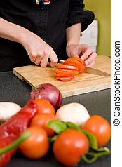 A detail image of a woman slicing tomatoes on a cutting board at home. - shallow depth of field with the focus on the tomato and knife