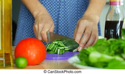 Slicing vegetables for salad. Woman crumbles ingredients with a knife
