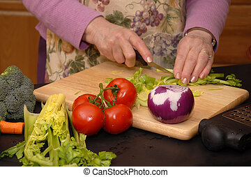 Senior woman's hands slicing raw vegetables on a cutting board.