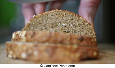 Slicing Whole Grain Bread On Wooden Table
