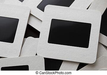 Old slide film transparencies in cardboard frames in pile, close up.