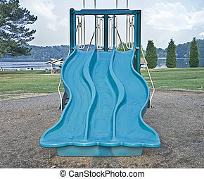 A large slide in a scenic playground area.