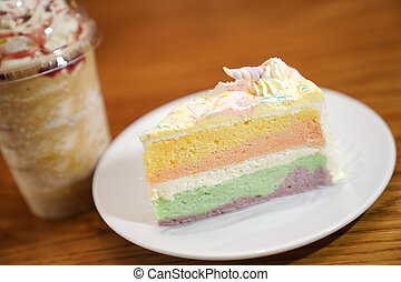 Slided rainbow cake decorate with unicorn horn on top next to coffee frappe. The cake is in a white disk on the wooden table and blur background.