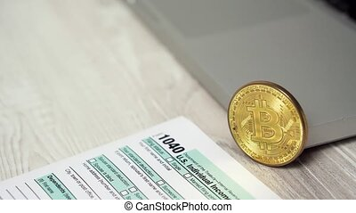 Slider shot of Bitcoin coin on the computer laptop next to 1040 Income Tax Return Refund Form concept. Bitcoins And Dollars On The Table 4k video