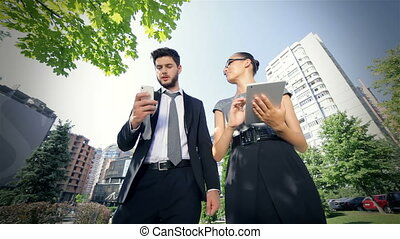 Sliding camera of couple standing together, work on the tablet, and take call