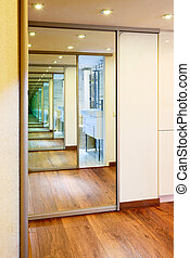 Sliding-door mirror wardrobe in modern hall interior with infinity reflections
